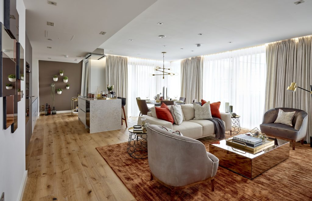 furnished living room with wooden floors, grey chairs and red cushions